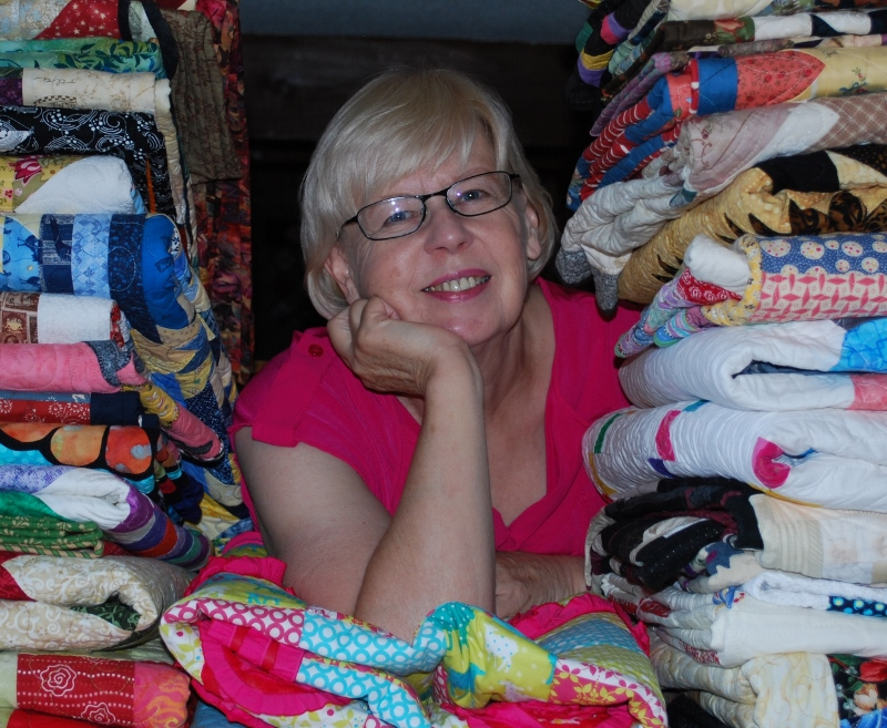 Photo of Bev with lots of quilts!